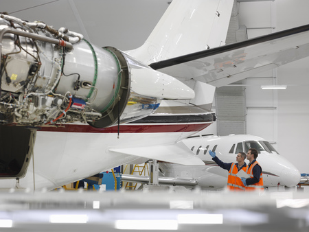 coordinating: Engineers inspect jet aircraft