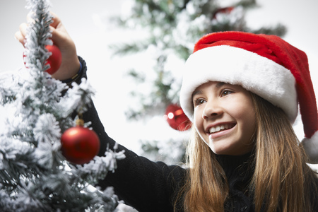 Girl decorating the christmas tree LANG_EVOIMAGES