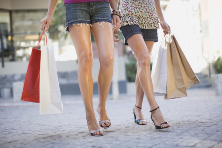 low section: Womens legs with shopping bags