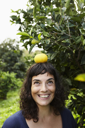 enthusiastically: Woman balancing mandarin on her head LANG_EVOIMAGES