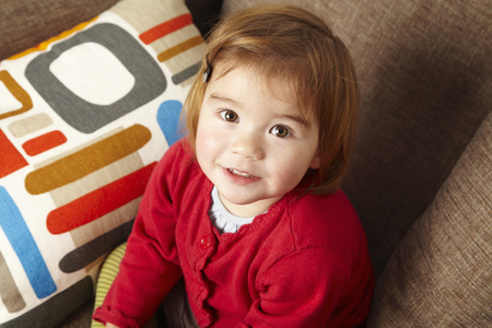 fulfill: Young girl sitting on sofa looking up LANG_EVOIMAGES