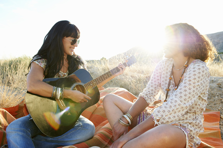 remoteness: Women playing the guitar in the grass LANG_EVOIMAGES