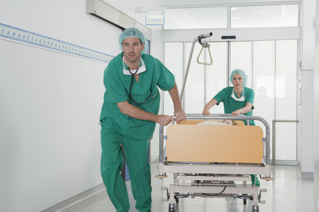 operation gown: Medical team in scrubs with bed in hall LANG_EVOIMAGES