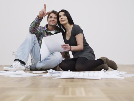 Paar sitzt mit Grundrissen in leerer Woh