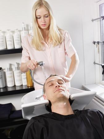 saturating: Hairdresser washing man's hair