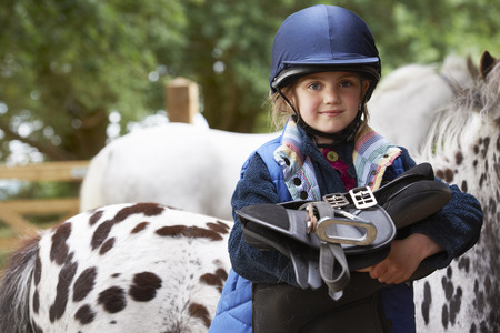 Young girl holding a saddle with ponies