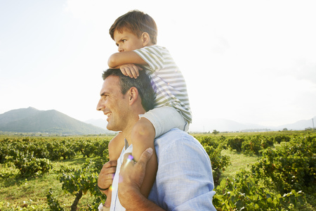 poppa: Father and son piggy backing in vineyard