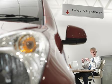 flogging: Salesman at desk in car dealership