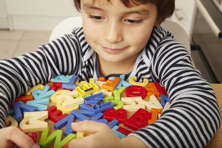leisurely: Boy playing with letters in kitchen LANG_EVOIMAGES