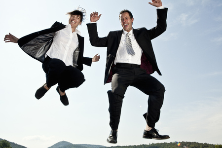 Businesswoman and businessman jumping