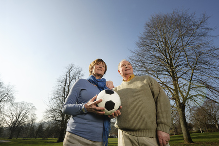 retiring: Older couple playing with soccer ball
