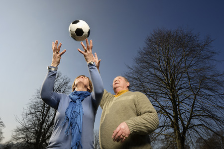 tosses: Older couple playing with soccer ball