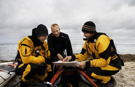 agachado: 3 hombres mirando el mapa