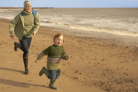 pursued: Woman,young boy running on beach. Fall