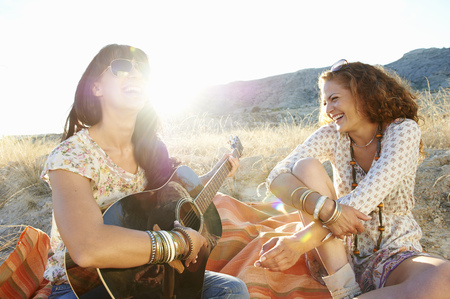 entertainers: Women playing the guitar in the grass LANG_EVOIMAGES