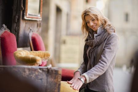 Woman marveling at antique furniture LANG_EVOIMAGES