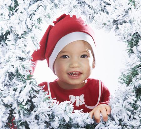 guirnaldas de navidad: Baby girl looking through the snowy tree LANG_EVOIMAGES