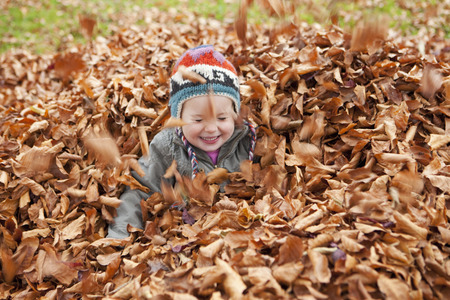 Girl playing in the leaves