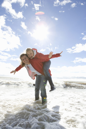 enthusiastically: Mom and daughter at beach piggyback ride