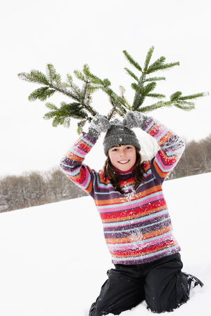 Girl holding fir branches on her head