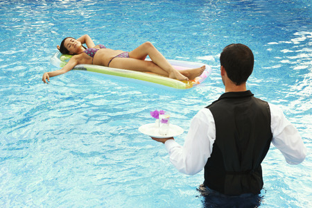 Waiter serving drinks to girl in a pool