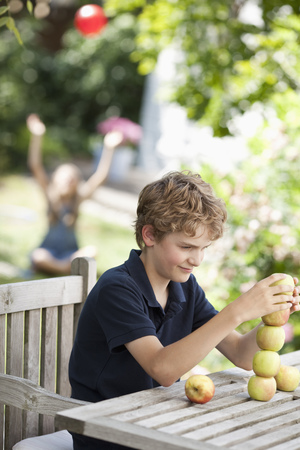 Boy building a tower out apples LANG_EVOIMAGES