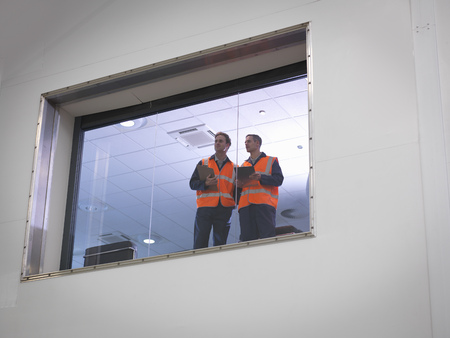 mans watch: Engineers look out of window into hangar