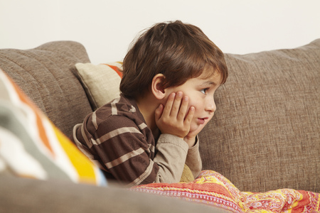 dubious: Boy on sofa staring at television LANG_EVOIMAGES