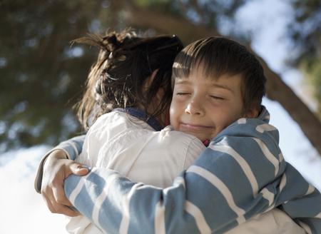 Boy hugging woman,smiling LANG_EVOIMAGES