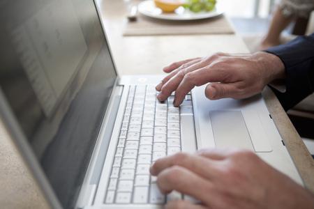 typist: Close up of businessman using laptop LANG_EVOIMAGES