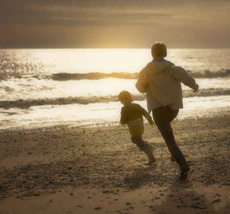 pursued: Woman chasing young boy on beach. Autumn
