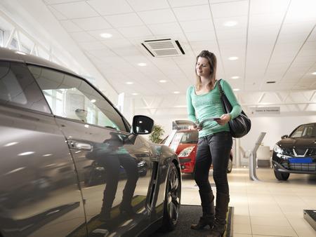 Female customer looks at car
