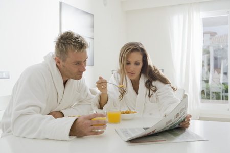 gals: Young couple reading paper at breakfast