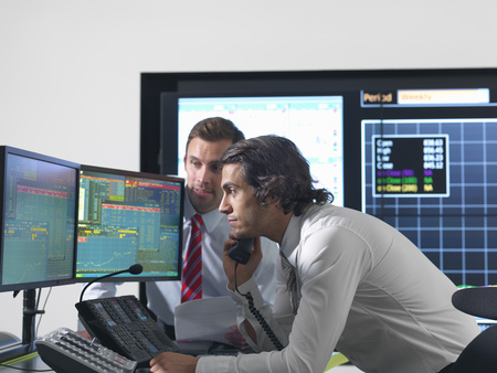 strategize: Financial traders with screens
