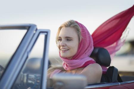 wind blown hair: Woman driving a convertible car LANG_EVOIMAGES