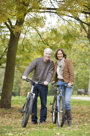 ceasing: Older man and woman cycle in the park LANG_EVOIMAGES
