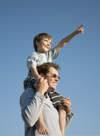 low spirited: Boy on Dads shoulders,looking at view