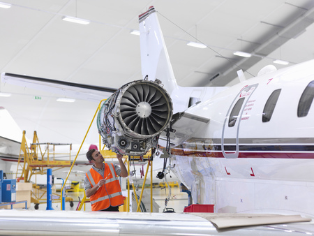 Engineer inspects jet engine LANG_EVOIMAGES
