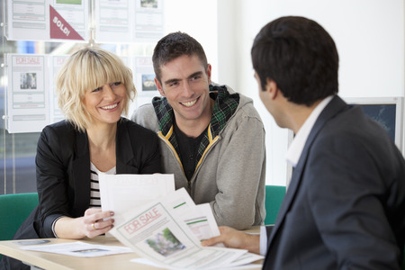 enthusiastically: Couple visiting estate agents office