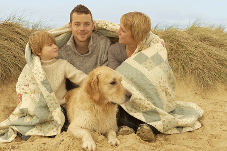 Family with dog,under quilt,on beach