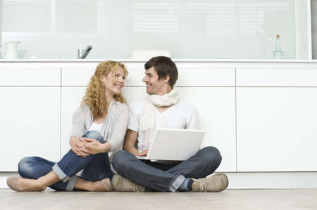 uses: Couple with laptop on kitchen floor