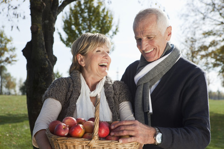 assembled: Senior couple with basket of apples