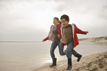 low spirited: Mother and son running together on beach LANG_EVOIMAGES