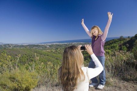 Mother photographing daughter with view