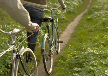 pursuing: Couple pushing old bicycles,close-up