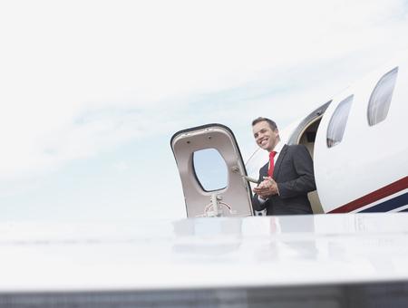 Businessman exiting corporate jet LANG_EVOIMAGES
