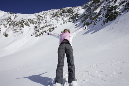 enthusiastically: Woman skiing backwards down slope