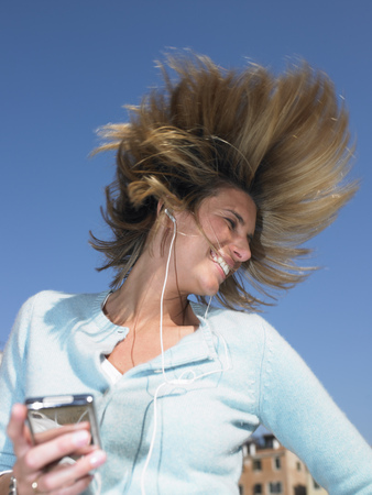 enthusiastically: Woman listenning to mp3 player,dancing LANG_EVOIMAGES