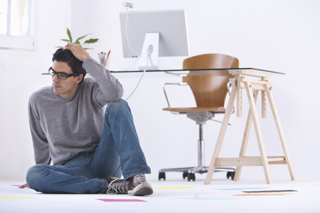 Man sitting on the floor in a office thinking