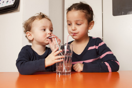 refreshed: Boy and girl drinking water with straws LANG_EVOIMAGES